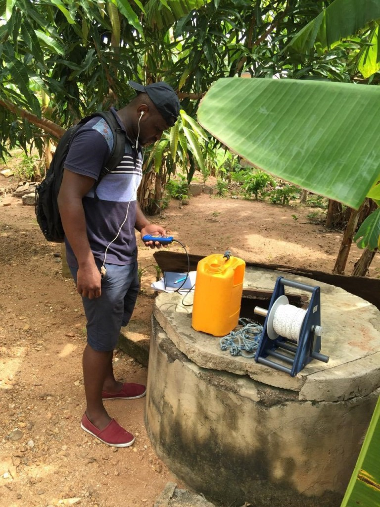 Obed taking a sample and measuring chemical parameters in the field
