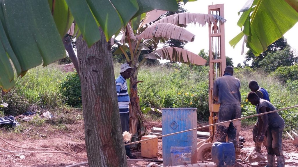 John Okwi (left, with hat), the owner of PAT-DRILL Uganda, is supervising his team of drillers using a PAT-301 to drill through the weathered basement near the top of Makerere hill
